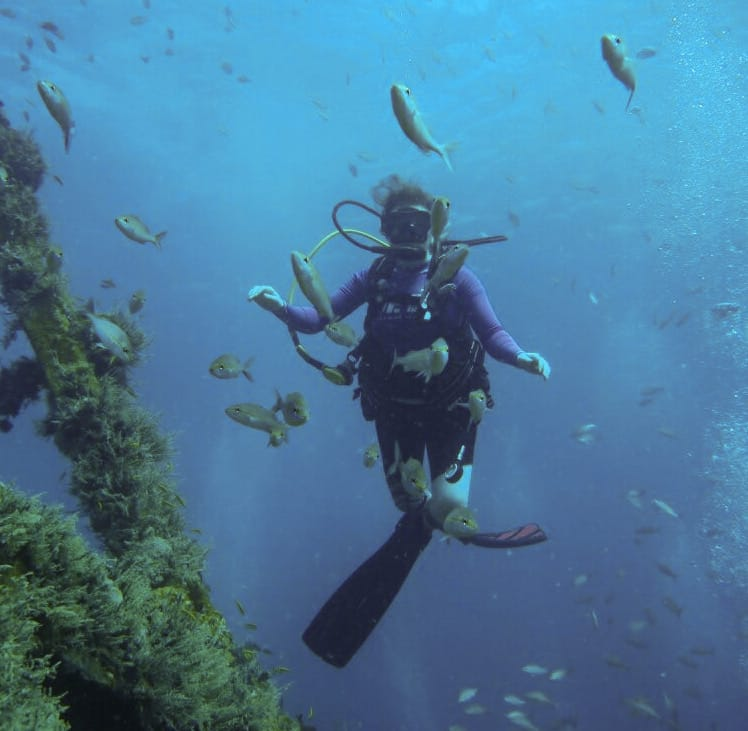 Amber scuba diving with fish in St Kitts